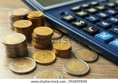 Money concept. Black calculator with coins on wooden table - stock photo