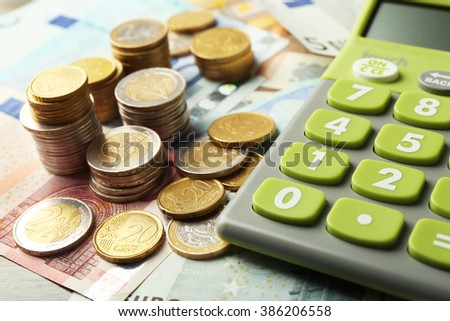 Money concept. Green calculator with banknotes and coins, close up - stock photo