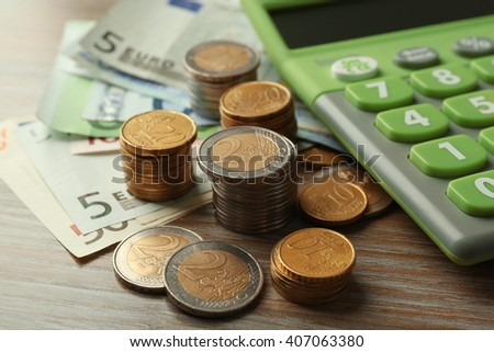 Money concept. Green calculator with banknotes and coins on wooden table - stock photo