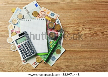 Money concept. Grey calculator with coins and notebook on wooden table - stock photo