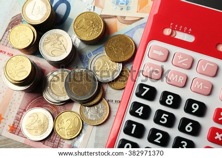 Money concept. Red calculator with banknotes and coins, close up - stock photo