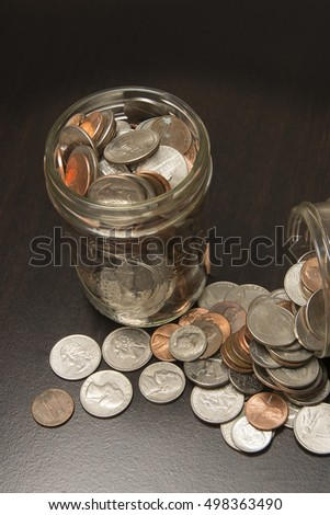 Money Currency spills out  of container/Spare Change/Coins in and out of jars