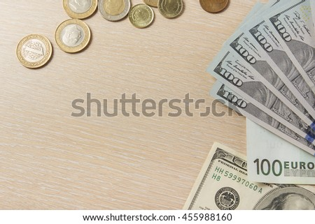 Money dollars euro cents on wooden table desk background with copy space for ad text - stock photo