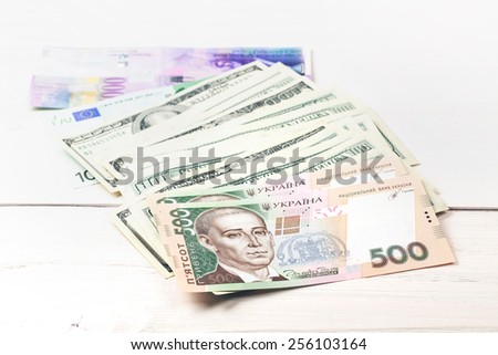 Money: dollars, UAH, the euro, and Swiss francs lying on white wooden table in a row - stock photo
