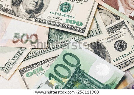 Money: dollars, UAH, the euro , and Swiss francs lying on white wooden table in a row - stock photo