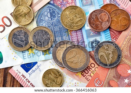 Money Euro banknotes and coins on wooden table, top view
