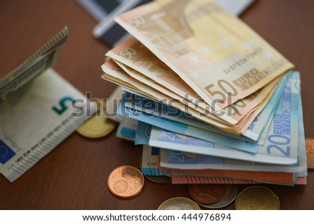 Money euro coins, banknotes and credit cards on wooden background - stock photo