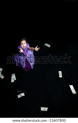 Money falling down and being caught by a pretty little girl.