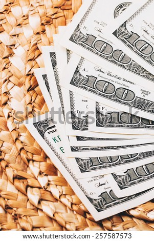 Money fan of dollars lying on Wicker surface