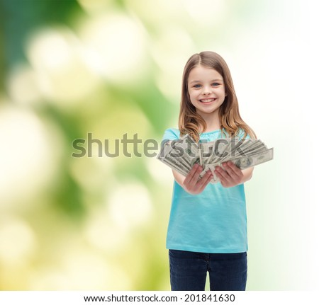 money, finances and people concept - smiling little girl giving dollar cash money - stock photo