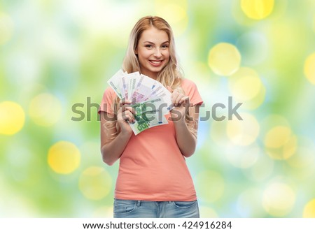 money, finances, investment, saving and people concept - happy young woman with euro cash money over summer green lights background - stock photo