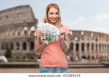 money, finances, travel, tourism and people concept - happy young woman with euro cash money over coliseum background - stock photo