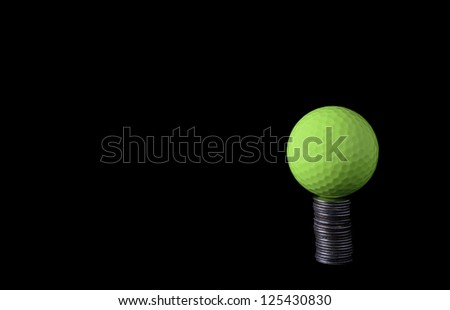 Money game: Yellow golf ball teed up on a stack of coins, isolated on black - stock photo