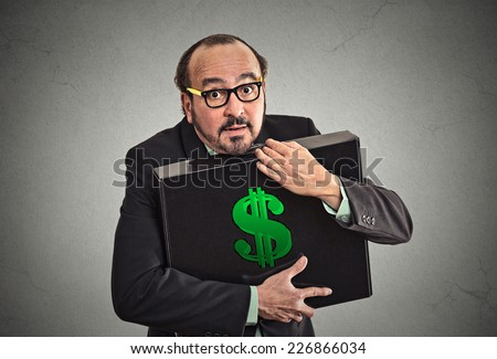 Money greed. Business man holding holding case with dollars tightly isolated on grey wall background. Worship, miser, excessive gain, finance concept  - stock photo