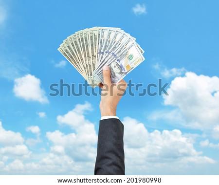 Money - hand holding United States dollar banknotes on blue sky background - stock photo