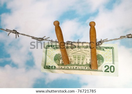 Money hanging on clothes pegs on barbed wire - stock photo