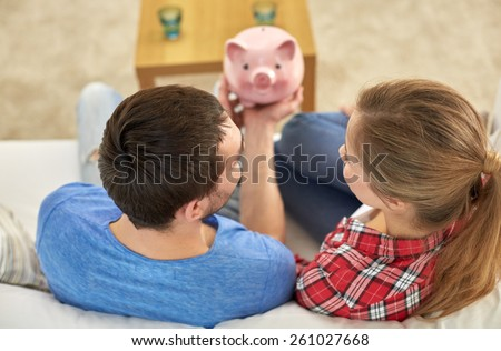 money, home, finance and relationships concept - close up of couple with piggy bank sitting on sofa - stock photo