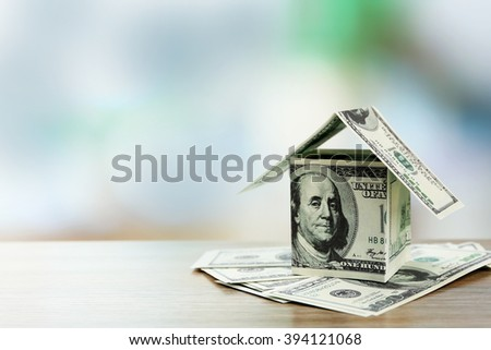 Money house on dollar bills on wooden table, close up - stock photo