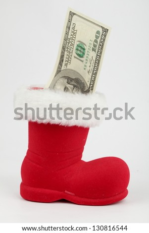 Money in a Christmas sock as a gift - stock photo