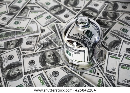 Money in a glass jar on the background of one hundred dollar bills. Fake money. Conceptual photo on the business theme. Shallow depth of field. Selective focus. - stock photo