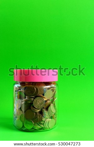 Money in a glass with a green background.