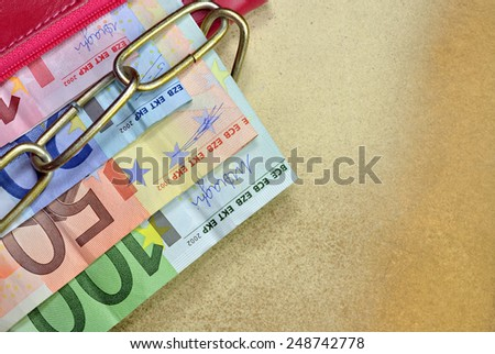 Money in a red chained wallet on yellow background - stock photo