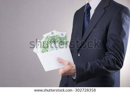 Money in an envelope in the hands of businessman on gray background