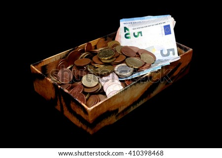 Money in an old box, banknotes and coins, isolated on black - stock photo