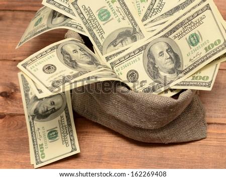 money in burlap sack on wooden background - stock photo