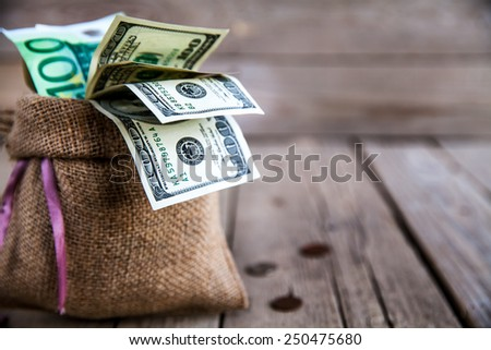 money in burlap sack on wooden background - stock photo