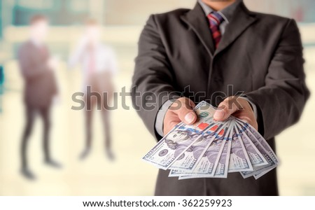 Money in Businessman hand , US dollar,investment, success and profitable business concepts