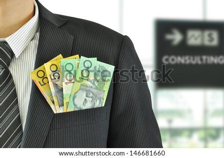 Money in businessman suit pocket - Australian Dollar bills - stock photo