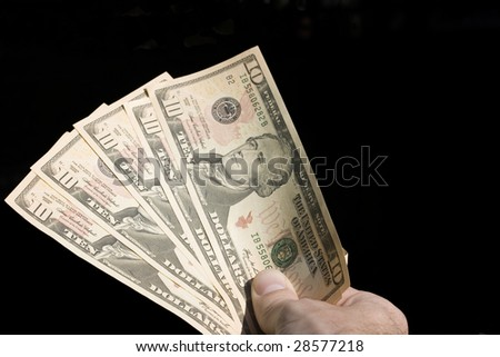 Money in hand, in a gesture as if giving or paying for something.  Its againt a black background - stock photo