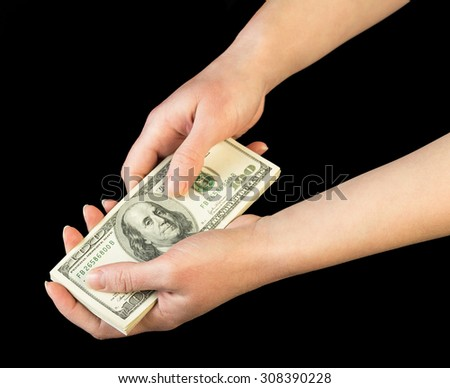 Money in human hands on black background