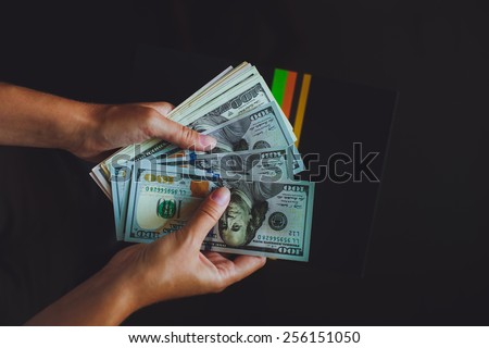 Money in human hands, women counting a lot of 100 dollars, with business folders , on a black background