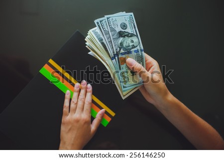 Money in human hands, women giving a lot of 100 dollars, with business folders , on a black background - stock photo
