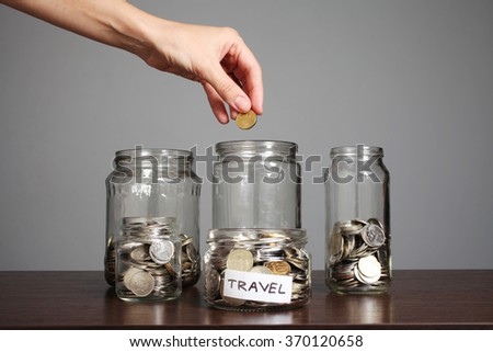 Money in jars, hand putting coins into jar - stock photo