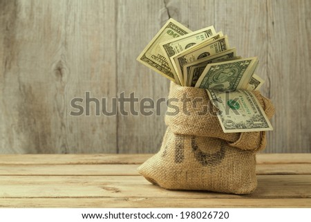 Money in sack on wooden table - stock photo