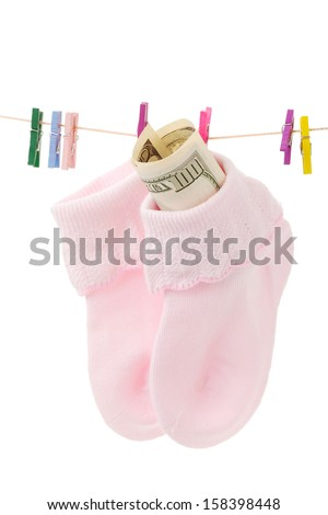 Money in sock on laundry line with pink clothespins,isolate d on white - stock photo