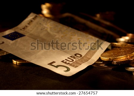 Money in the form of a Euro bill and some coins - stock photo
