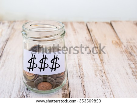 Money in the glass on wooden table background - stock photo
