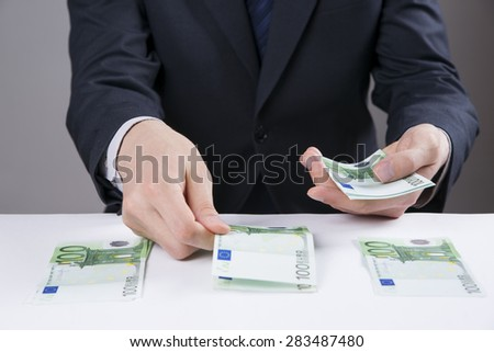 Money in the hands of the men. To count euro on gray background - stock photo