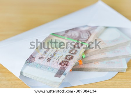 money in white envelope for someone on wood table - stock photo