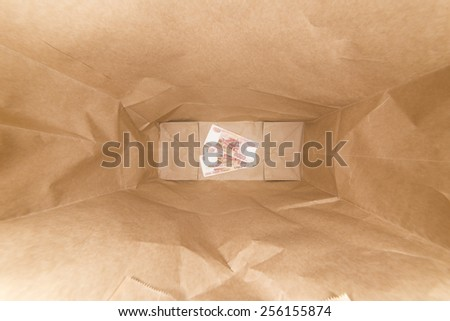 Money inside the crumpled paper bag. Three banknote of five thousand rubles. - stock photo