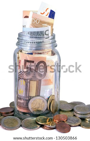 Money jar overflow with Euro bank notes and coins against white background.