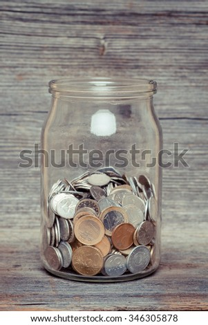 money jar with coins on wood table - stock photo