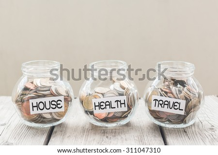 Money jar with coins on wood table , Saving Concept - stock photo