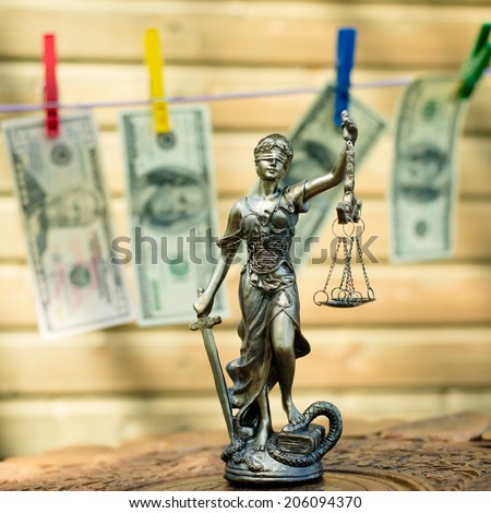money laundering concept: image of Themis goddess or lady justice holding scale blindfold & USD dollar bank notes hanging on the copy space background - stock photo