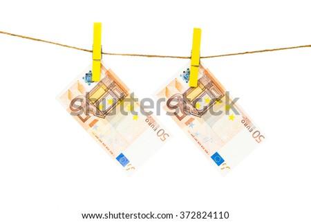Money laundering on clothesline isolated on white background.  Euro banknotes hanging - stock photo