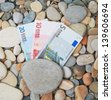 money lies on the seashore on a pebble beach - stock photo